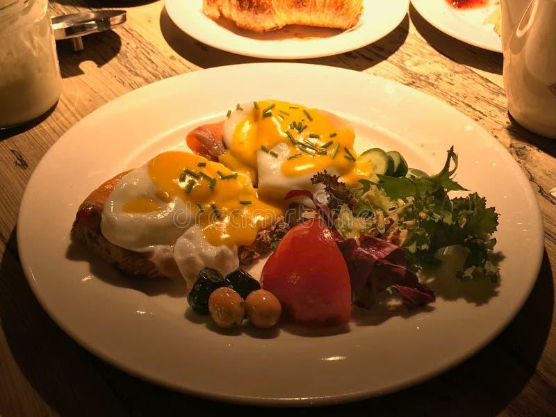 Eier Benedict mit geräuchertem Lachs auf gebratenem Brot dienten mit Olivenöl, Tomaten und frischem Salat stockfotos