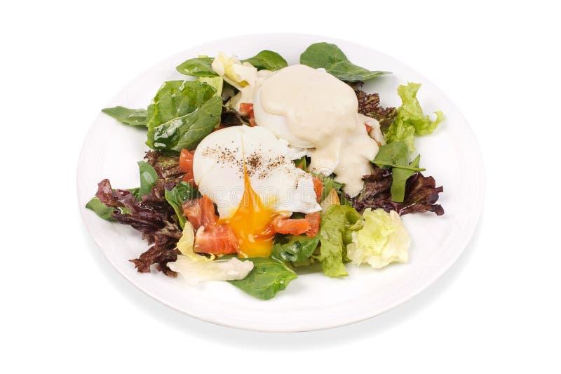 Eier Benedict rösteten englische Muffins, Lachse, poschierte Eier und köstliche butterartige Hollandaisesoße auf Salat lizenzfreie stockfotos