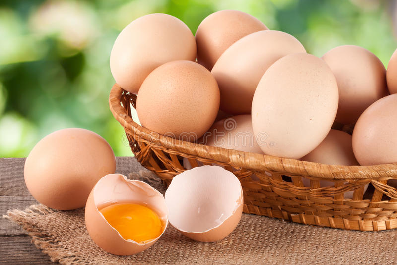 Eier in einem Weidenkorb auf einem hölzernen Brett mit unscharfem Gartenhintergrund lizenzfreies stockbild