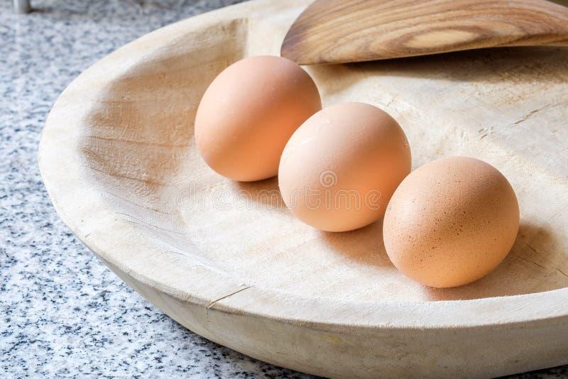 Eier in einer hölzernen Platte stockfotos