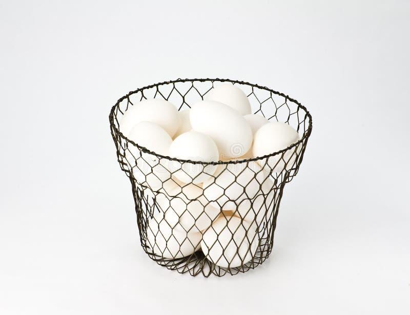 Eier im Drahtweinlese-Eikorb stockbild