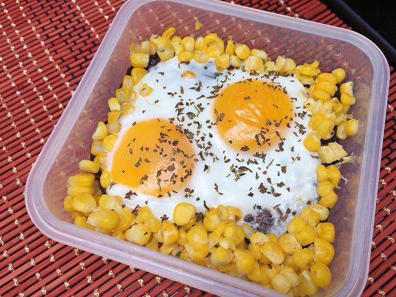 Eier mit Mais in den Holzkohlenbroten stockbild