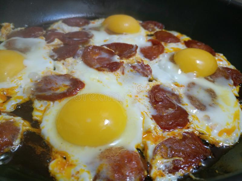 Eier und dünne Chorizoscheiben in einer heißen Wanne lizenzfreies stockfoto