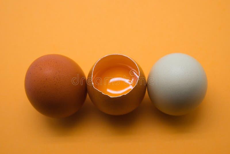 Eier und Eigelb auf dem gelben Hintergrund lizenzfreie stockfotos