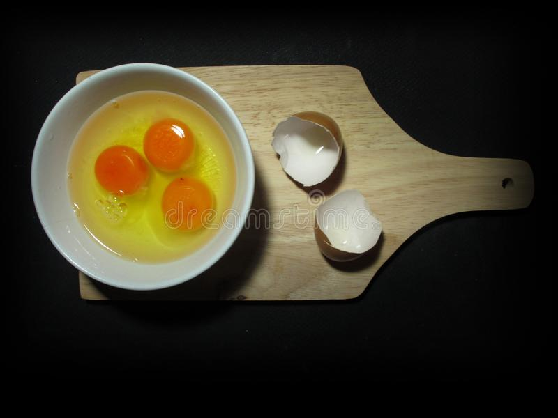 Eierdooier drie en wit in een kom op houten die hakbord met eierschaal, hierboven wordt genomen van stock foto's