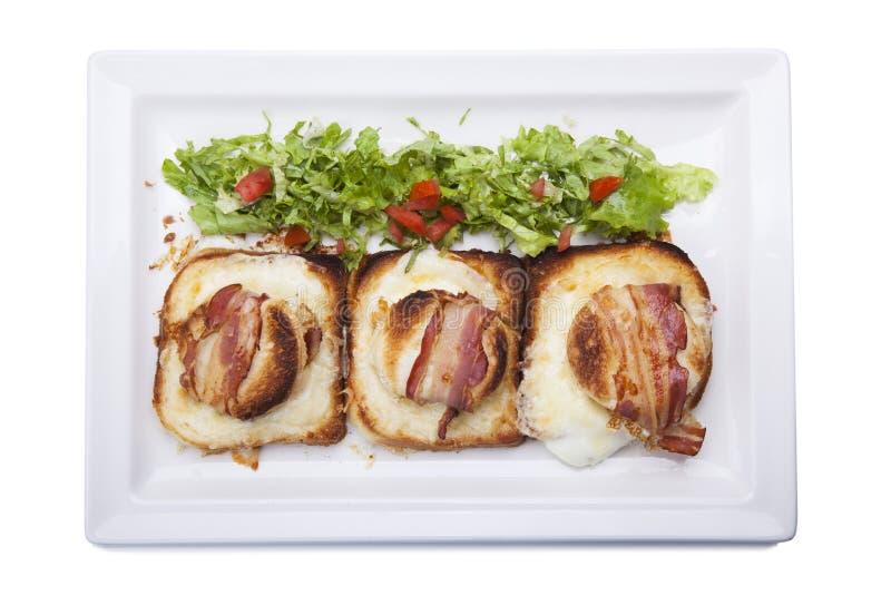 Eieren, bacon en cheve kaasontbijtsandwich met pan gebraden p stock foto