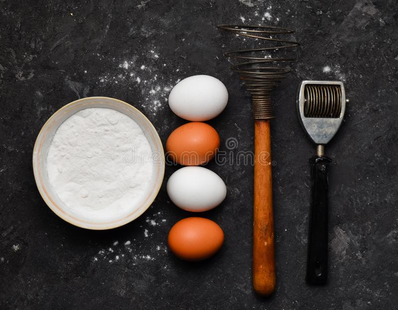 Eieren, bloem, keukengereedschap op een zwarte concrete lijst Ingrediënten voor deegwaren Het het koken procédé Hulpmiddelen om T royalty-vrije stock fotografie