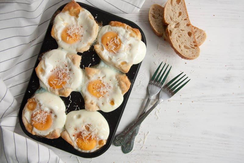 Eieren in een brood worden gebakken dat royalty-vrije stock afbeelding
