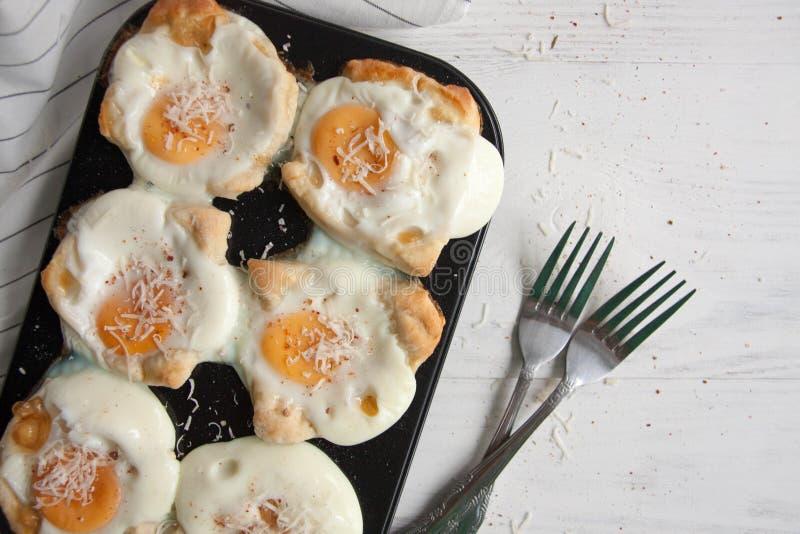Eieren in een brood worden gebakken dat stock afbeelding