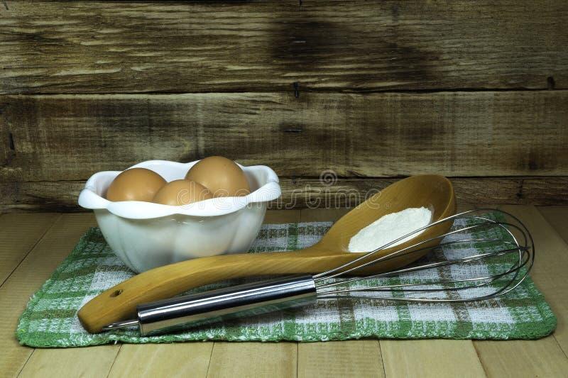 Eieren in een kom voor de voorbereiding van deeg met bloem en mixer op een rustieke houten achtergrond stock afbeelding