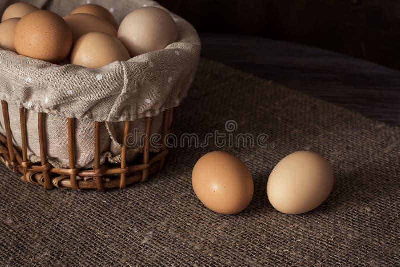 Eieren in een rieten mand op een houten lijst royalty-vrije stock afbeeldingen
