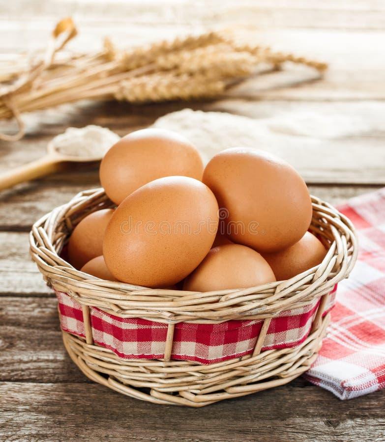 Eieren in een rieten mand op uitstekende houten lijst stock afbeelding