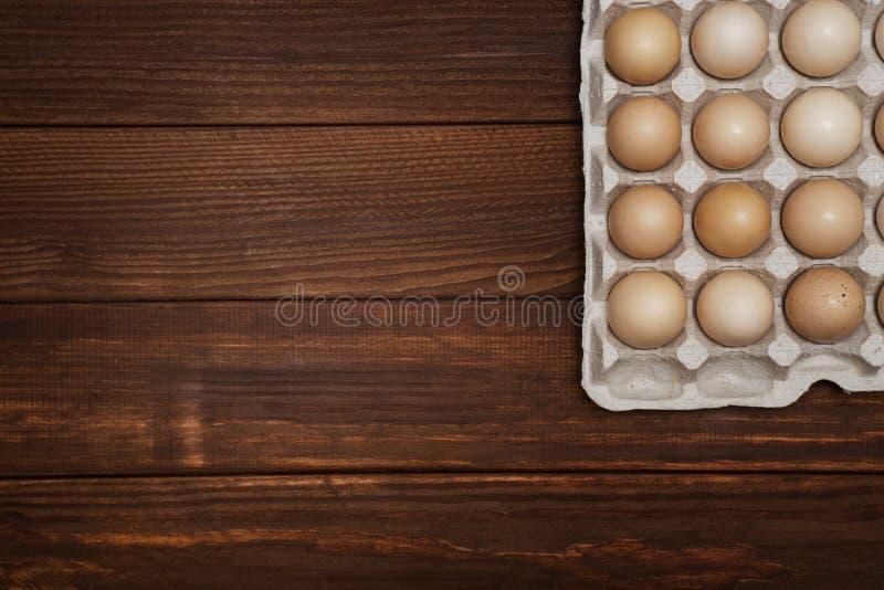 Eieren in een speciaal papierdienblad op een houten achtergrond Eieren op houten achtergrond royalty-vrije stock afbeelding