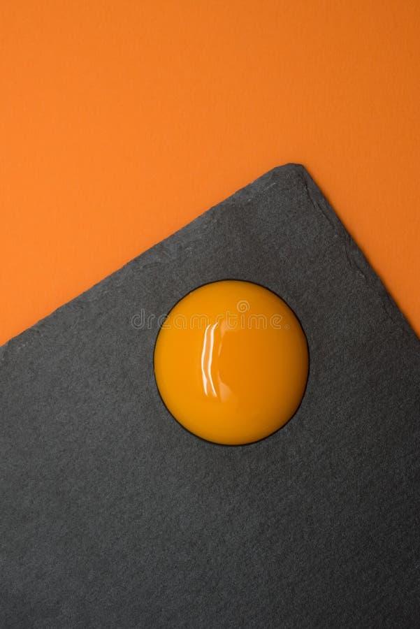Eieren en dooier op de gele achtergrond stock afbeeldingen