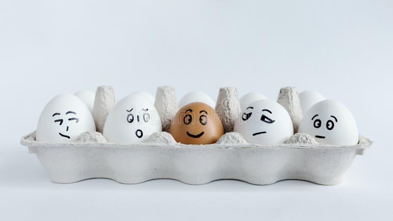 Eieren met grappige gezichten in het pakket op een witte achtergrond Pasen-Conceptenfoto Gezichten op de eieren stock foto