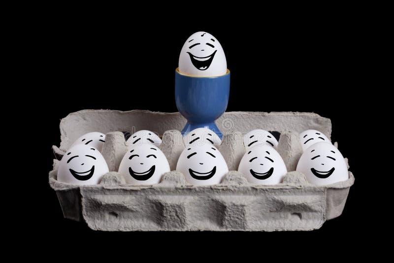 Eieren met smileygezichten in eierschaal met een werkgever over hun hoofd stock foto's