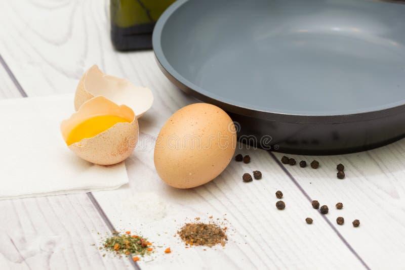 Eieren, olie, pan, kruiden, vork stock afbeelding