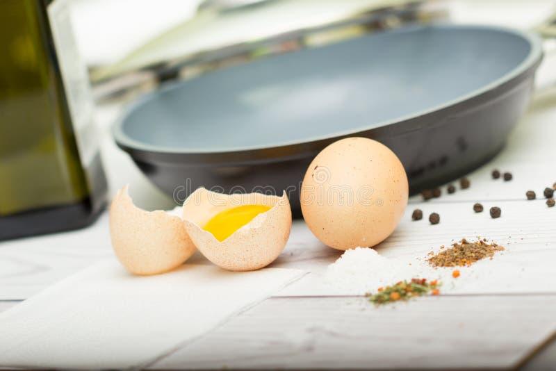 Eieren, olie, pan, kruiden, vork stock foto
