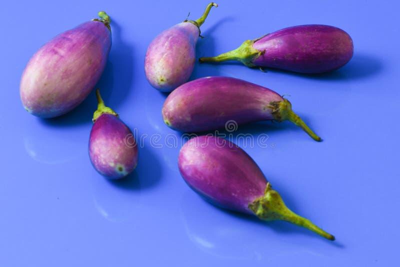 Eierplantaubergines op blauwe close-up worden geïsoleerd die als achtergrond stock fotografie