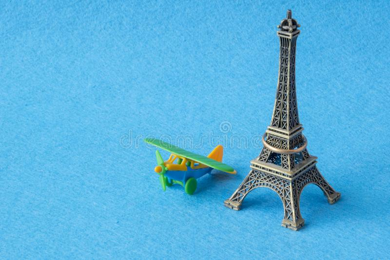 Eifel tower model with toy plane. Famous French landmark and airplane miniatures, paris souvenirs concept. Eifel tower model with little toy plane on blue royalty free stock images