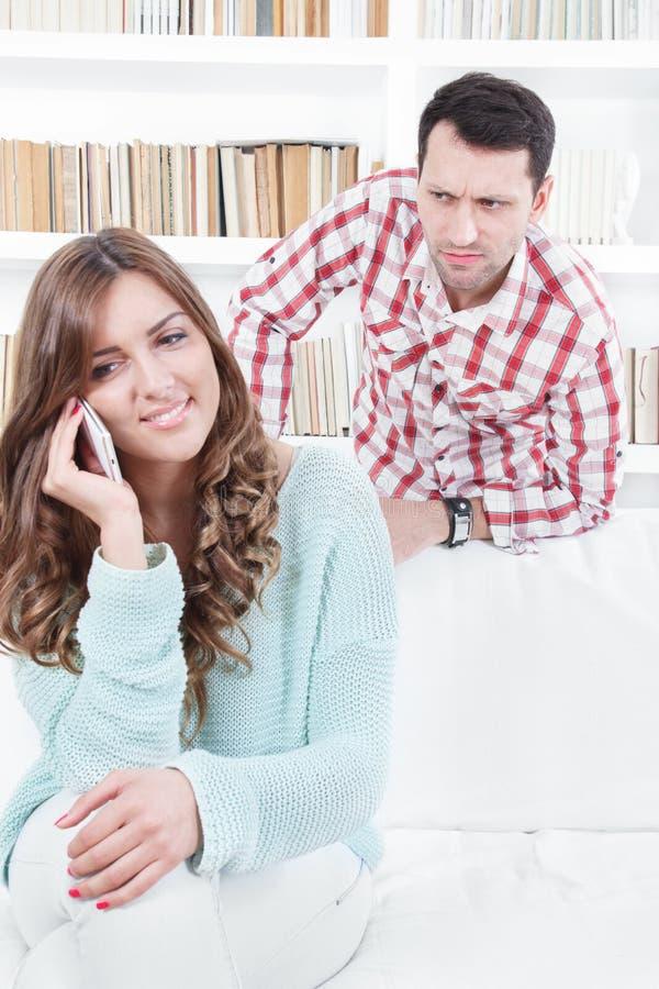 Eifersüchtiger besorgter Mann, der über der Schulter seiner Freundin blickt lizenzfreies stockfoto