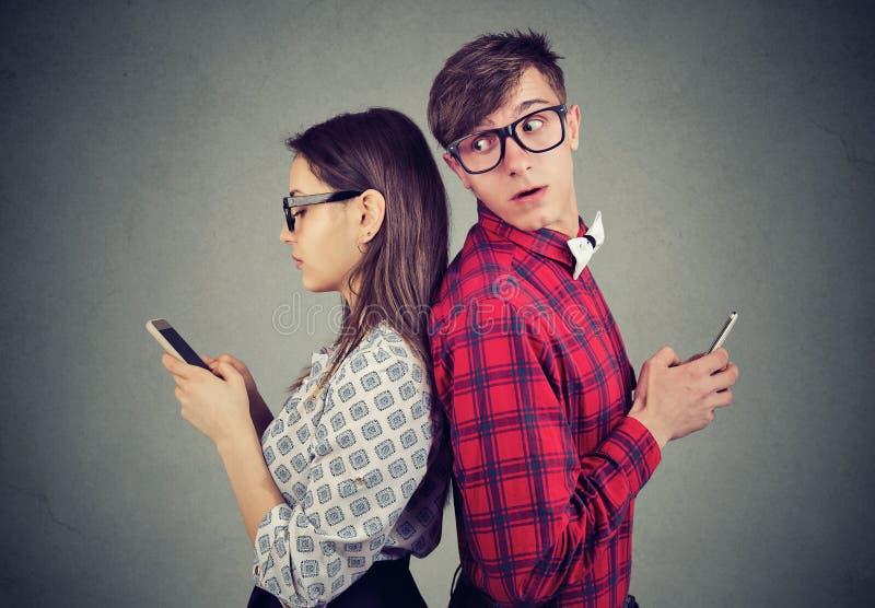 Eifersüchtiger Mann, der über seiner Schulter seinem Freundintelefon versucht, zu sehen betrachtet, was sie simst lizenzfreies stockbild