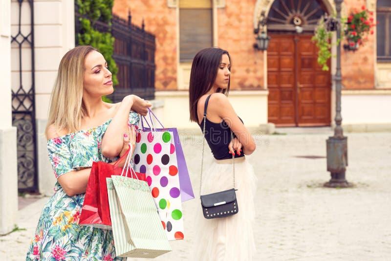 Eifersüchtiges Fraueneinkaufen und -argumentierung stockbilder