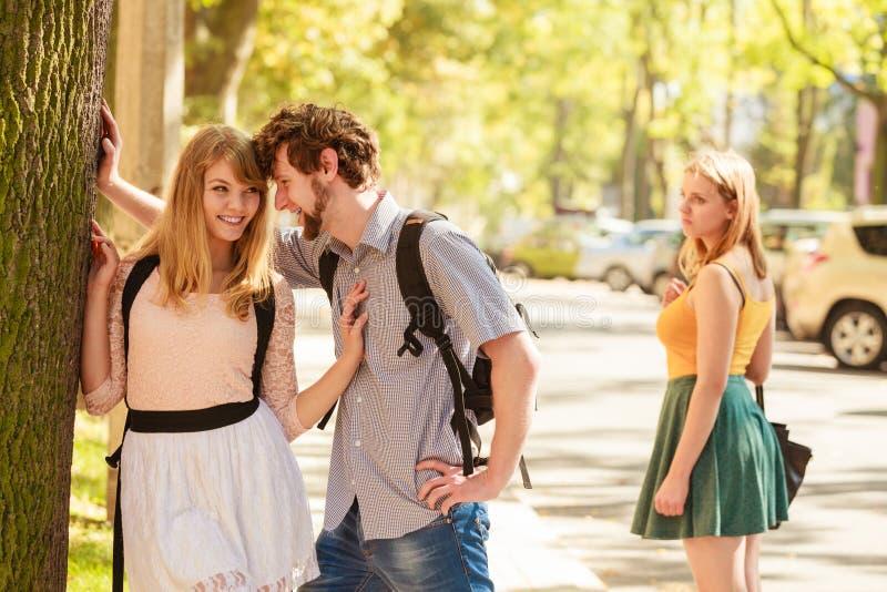 Eifersüchtiges Mädchen, welches die Flirtpaare im Freien betrachtet lizenzfreies stockfoto