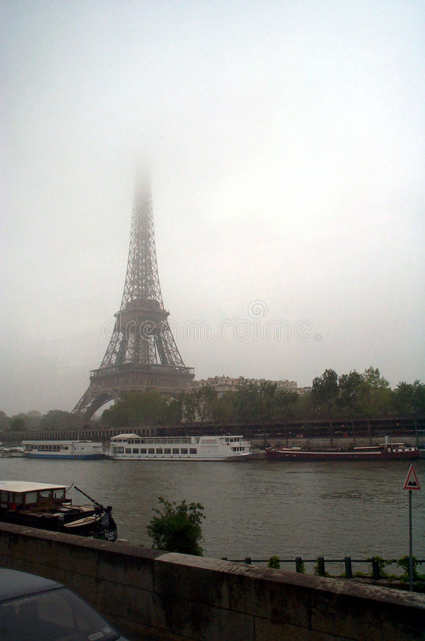 Eiffel tower against cloudy skies stock photography