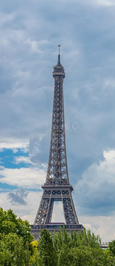 Eiffel Tower behind the trees against the backdrop of a bright cloudy sky royalty free stock photography