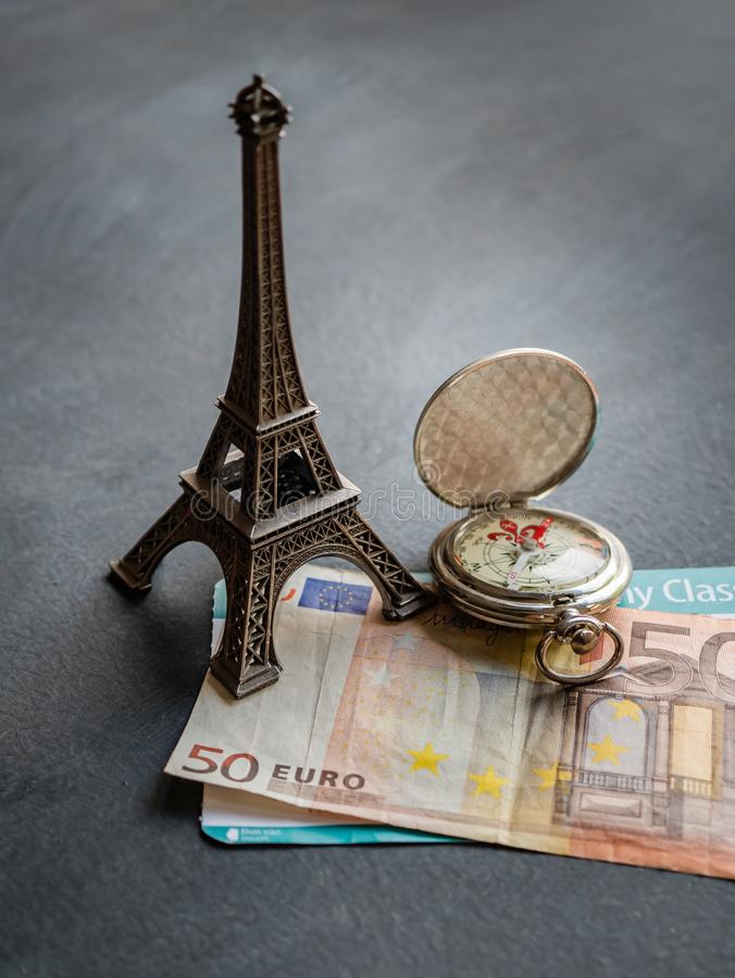 Eiffel tower with 50 euro banknote and boarding pass. Travel concept - Eiffel tower with 50 euro banknote and boarding pass finance journey map passenger sign royalty free stock photo