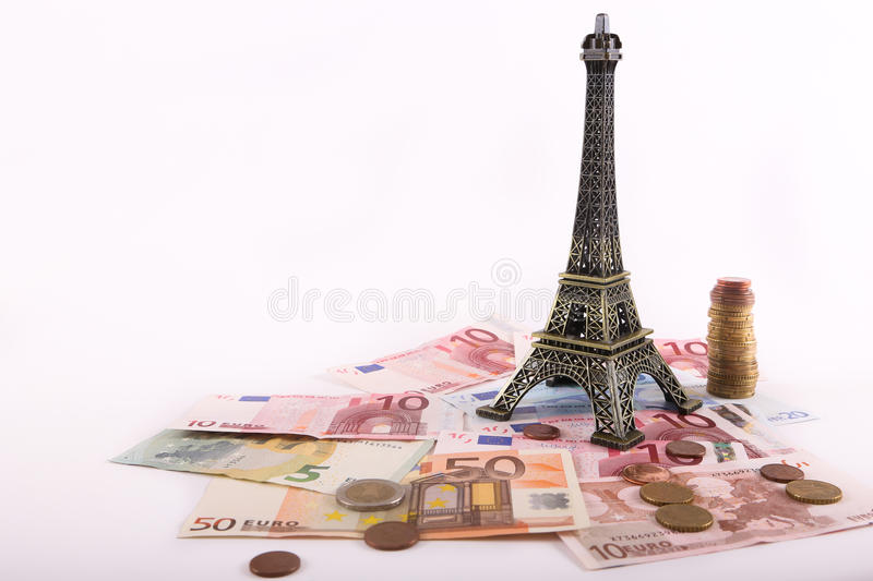 Eiffel tower with Euros banknotes. Paris - Eiffel tower with Euros banknotes and coins over white background stock images