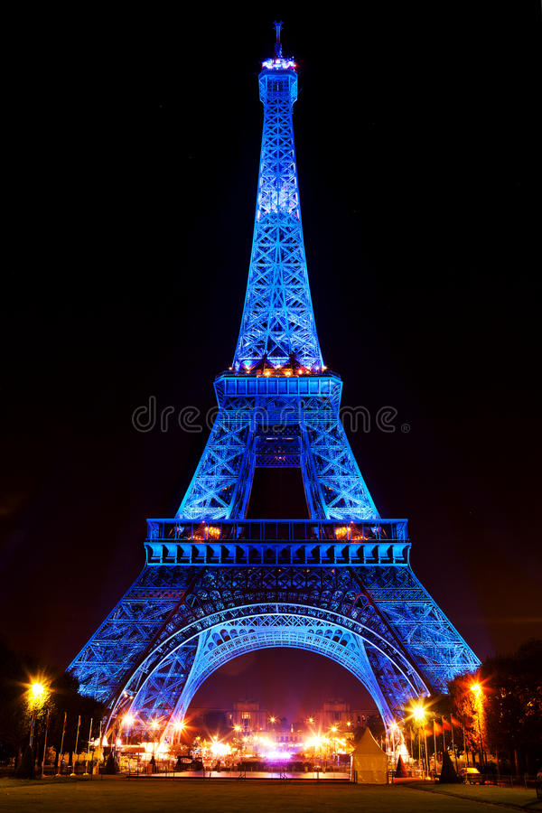 Eiffel Tower glowing blue illuminated at night in Paris, France.  royalty free stock photography