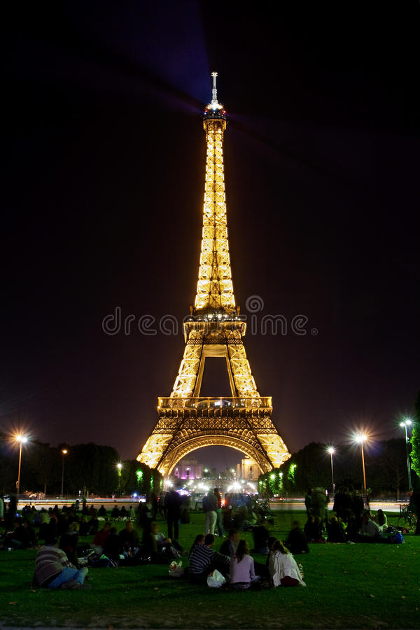 Eiffel tower by night and people on the grass royalty free stock photo