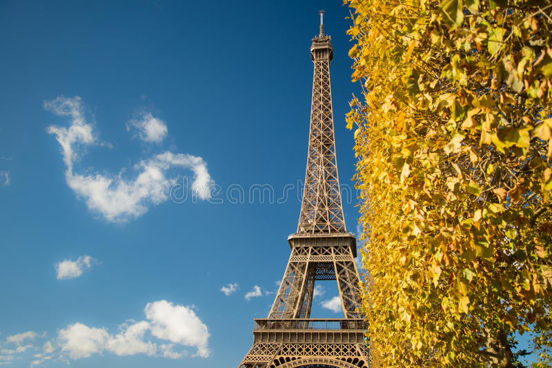 Eiffel Tower over blue sky and fall leaves. Eiffel Tower over blue sky and fall yellow leaves royalty free stock photography