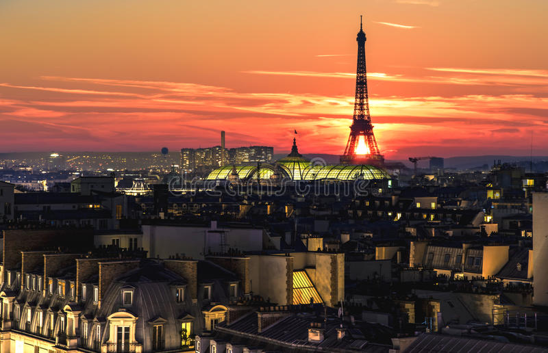 Eiffel tower over the roofs crowd. Bloody red color sunset over Paris and the Eiffel tower in Paris, France stock photos