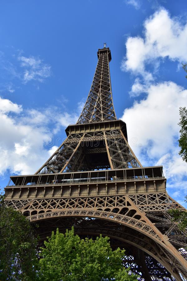 Eiffel Tower, Paris, France. Perspective from below. Trees and blue sky with clouds. royalty free stock photos