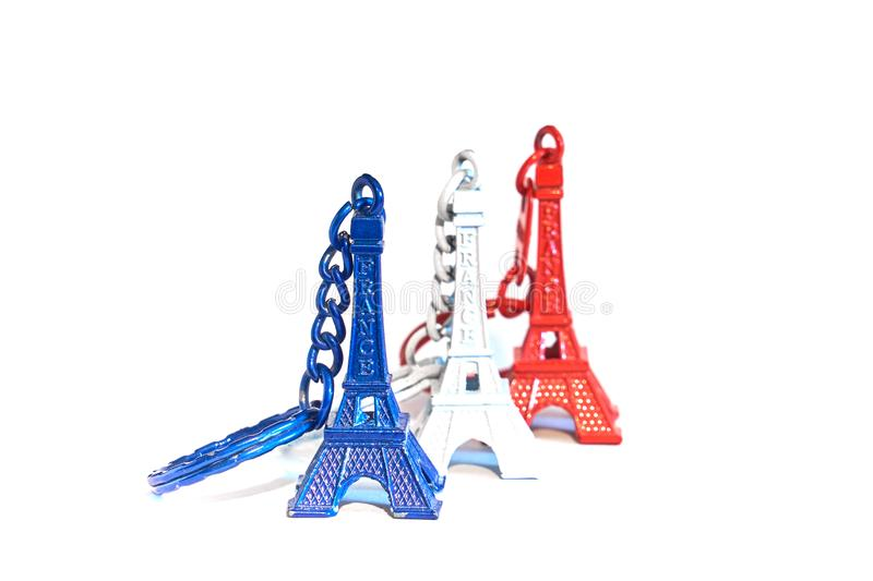 Eiffel tower souvenir keychains in colors of flag of France. Eiffel tower souvenir keychains in colors of flag of France isolated on white stock photography