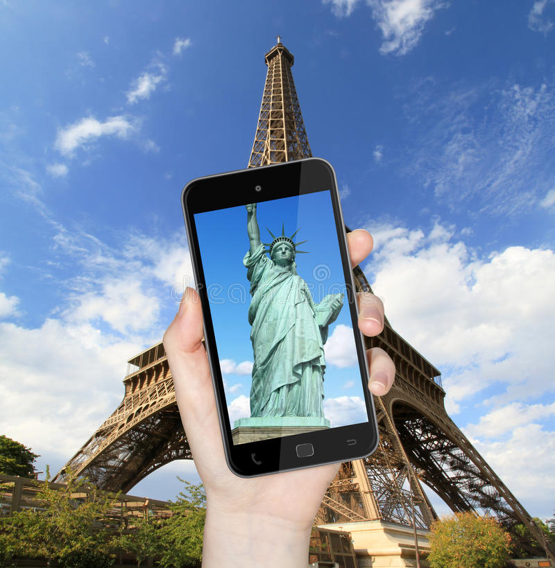 Eiffel Tower and statue of liberty taken with mobile phone. Hand taking a picture with mobile phone of the eiffel tower with statue of liberty on the screen vector illustration