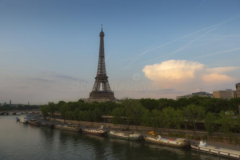 Eiffel Tower, a wrought-iron lattice tower on the Champ de Mars in Paris, France. Photographed at sunset from a bridge over the Seine River, with blue skies royalty free stock photography