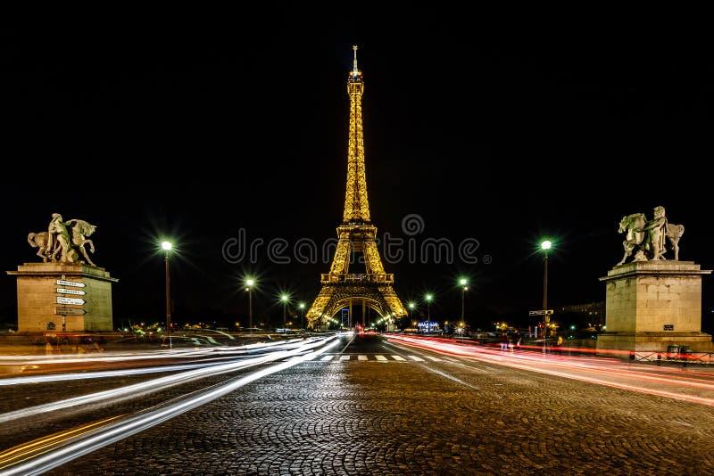 Eiffeltorn- och trafikljusslingor i natten, Paris, franc arkivfoton