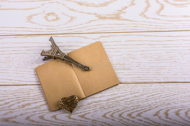 Eiffelturmminiatur und ein Stahlherz auf einem braunen Notizbuch an lizenzfreie stockfotografie
