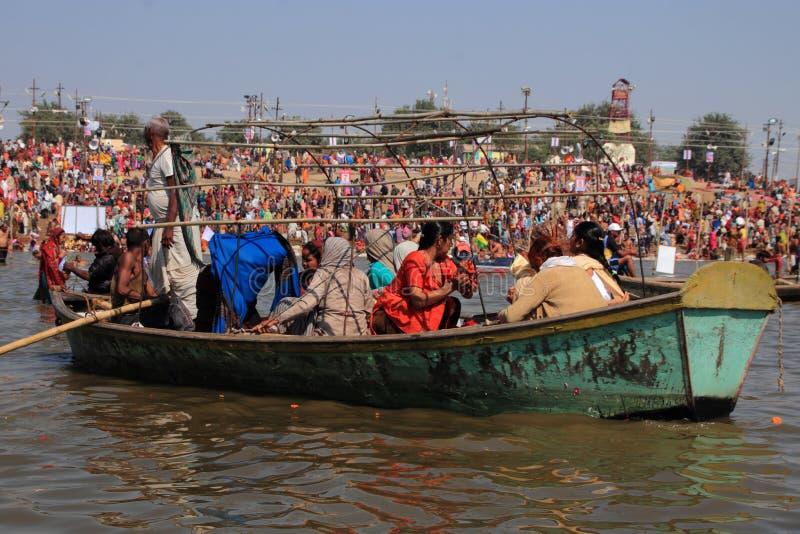 Eifrige Anhänger reisen in Boot, um Bad während des Kumbh Mela zu nehmen stockbilder