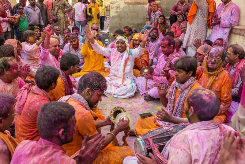 Eifrige Anhänger spielen die Musik, die mit Farben während der Holi-Feier in Barsana, Indien umfasst wird stockbilder