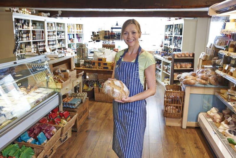 Eigenaar die van Delicatessen zich in het Brood van de Winkelholding van Brood bevinden royalty-vrije stock foto's