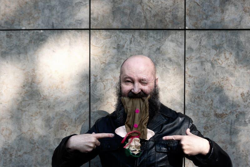 Eigenaardige gekke kunstenaarspoppenkastspeler met baard, met verbaasde uitdrukking, spelen met een rovershandpop stock foto