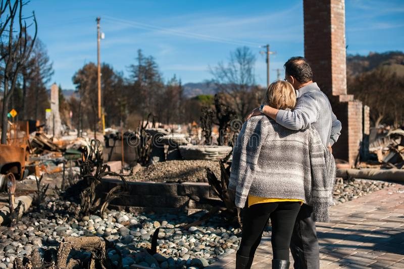 Eigenaars, die gebrand en geruïneerd huis en werf na brand controleren stock foto's