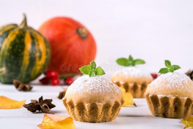 Eigengemaakt baksel in de herfststijl Heerlijke cupcakes op een houten raad met pijpjes kaneel, anijsplantsterren, pompoenen stock afbeelding