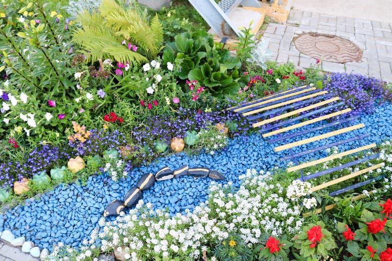 Eigengemaakt bloembed met mooie cet en installaties, greens en groen gras stock afbeelding