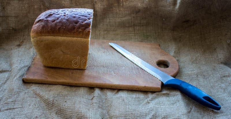 Eigengemaakt brood op een houten plank met een mes op de achtergrond van jute stock afbeeldingen